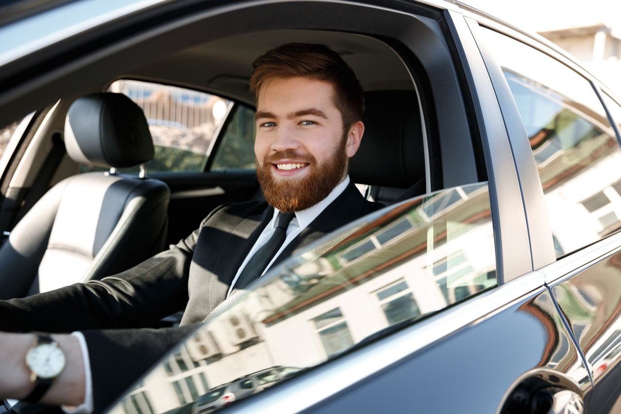 side-view-of-smiling-business-man-driving-car-PEV8CNV